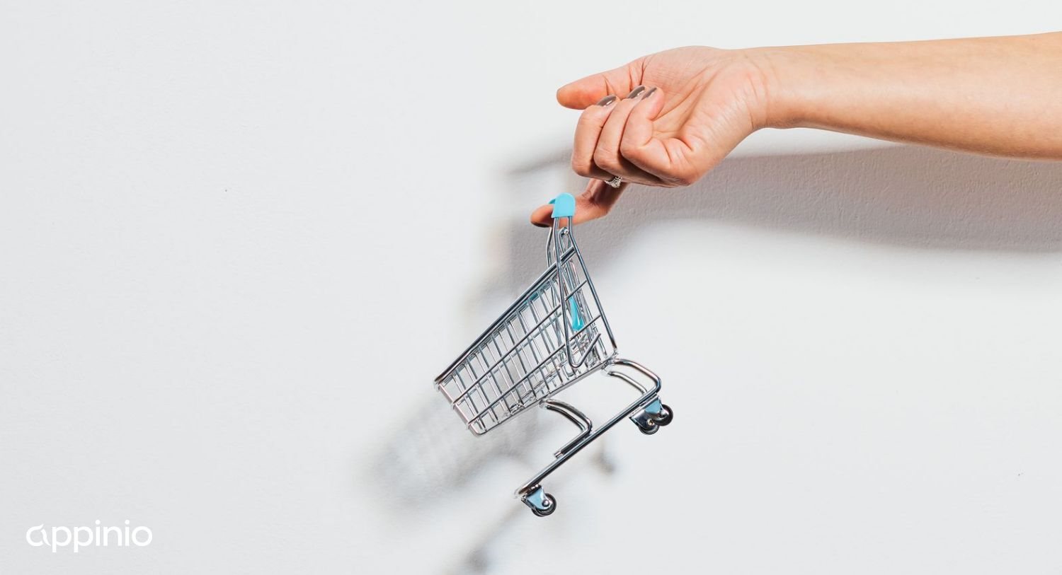 A miniature shopping cart being lifted by a person's hand.